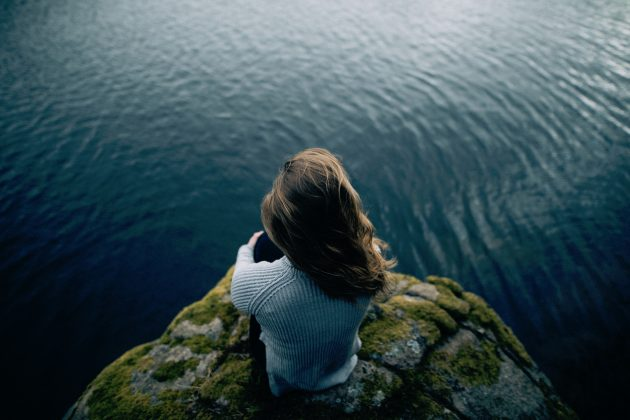 Girl sitting on a rock alone overlooking open water