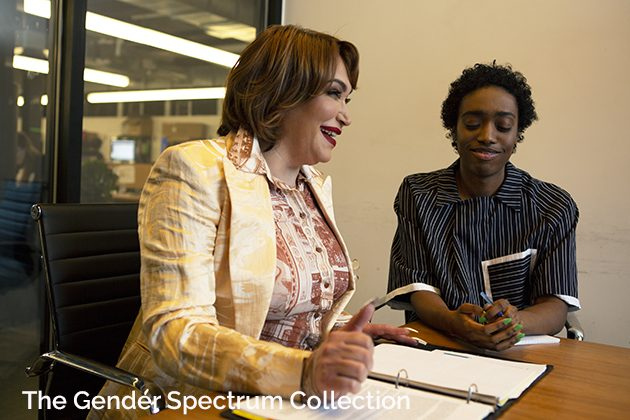 Two colleagues, a transgender woman and a non-binary person, laughing in a meeting at work copy
