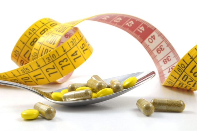 measuring tape with tablets and spoon - diet concept